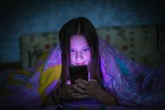 Mała śliczna dziewczyna patrzeje smartphone w łóżku przy nocą pod koc zdjęcie royalty free