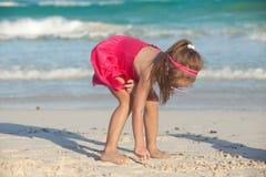Mała śliczna dziewczyna rysuje na białym piasku przy Obraz Stock
