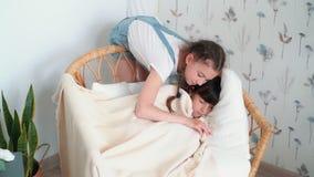 Mała śliczna dziewczyna spadał uśpiony w krześle, siostra zakrywa jej koc, zwolnione tempo zbiory wideo
