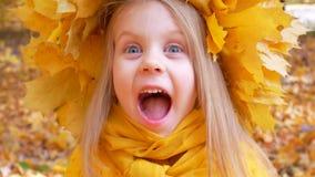 Mała śliczna dziewczyna w żółtym szaliku i wianku jest uśmiechnięta przy parkiem w jesieni zbiory