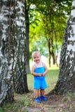 Mała śliczna dziewczyna w błękitnym kostiumu chuje w lato parku Fotografia Stock