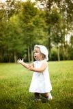 Mała śliczna dziewczyna w biel sukni biega w lato parku Zdjęcia Royalty Free