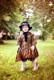 Mała śliczna dziewczyna w kapeluszu i pelerynie z torebką w autmn pa Obrazy Royalty Free