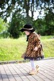 Mała śliczna dziewczyna w kapeluszu i pelerynie z torebką w autmn pa Obraz Stock
