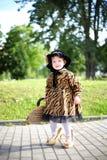 Mała śliczna dziewczyna w kapeluszu i pelerynie z torebką w autmn pa Zdjęcia Stock