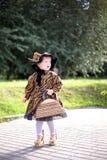 Mała śliczna dziewczyna w kapeluszu i pelerynie z torebką w autmn pa Zdjęcie Stock
