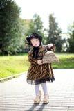 Mała śliczna dziewczyna w kapeluszu i pelerynie z torebką w autmn pa Zdjęcia Royalty Free