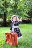 Mała śliczna dziewczyna w kapeluszu i pelerynie z walizką w autmn p Zdjęcie Royalty Free