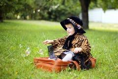 Mała śliczna dziewczyna w kapeluszu i peleryny obsiadaniu na walizce w a Obrazy Royalty Free