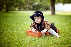 Mała śliczna dziewczyna w kapeluszu i peleryny obsiadaniu na walizce w a Zdjęcia Stock
