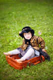 Mała śliczna dziewczyna w kapeluszu i peleryny obsiadaniu na walizce w a Obrazy Stock
