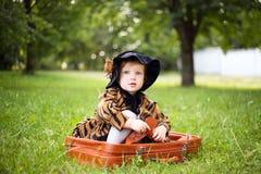 Mała śliczna dziewczyna w kapeluszu i peleryny obsiadaniu na walizce w a Zdjęcia Royalty Free