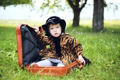 Mała śliczna dziewczyna w kapeluszu i peleryny obsiadaniu na walizce w a Zdjęcie Stock