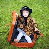 Mała śliczna dziewczyna w kapeluszu i peleryny obsiadaniu na walizce w a Fotografia Stock