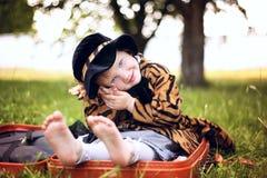 Mała śliczna dziewczyna w kapeluszu i peleryny obsiadaniu na walizce w a Fotografia Royalty Free
