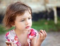 Mała śliczna dziewczyna z czekoladą w parku Zdjęcia Stock