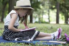 Mała śliczna dziewczyna z kapeluszowym obsiadaniem w naturze na trawie, pisze obrazy royalty free