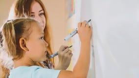 Mała śliczna dziewczyna z nauczyciela writing na blackboard w sala lekcyjnej obraz stock