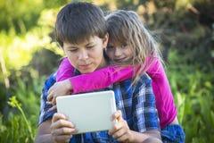 Mała śliczna dziewczyna z starym bratem trzyma pastylkę Obraz Stock