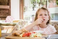 Mała Śliczna dziewczyny łasowania grzanka z sałatką przy śniadaniem obraz stock