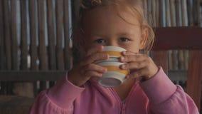 Mała śliczna dziewczyny woda pitna i patrzeć kamerę salową, zwolnione tempo zdjęcie wideo