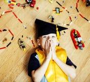Mała śliczna preschooler chłopiec wśród zabawki lego edukaci w magisterski kapeluszowy uśmiecha się pozować emocjonalny w domu, s Zdjęcia Stock