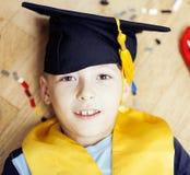 Mała śliczna preschooler chłopiec wśród zabawki lego w magisterski kapeluszowy uśmiecha się pozować emocjonalny w domu, stylu życ Zdjęcia Stock