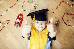 Mała śliczna preschooler chłopiec wśród zabawki lego w magisterski kapeluszowy uśmiecha się pozować emocjonalny w domu, stylu życ Fotografia Royalty Free