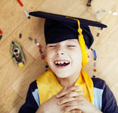 Mała śliczna preschooler chłopiec wśród zabawki lego w magisterski kapeluszowy uśmiecha się pozować emocjonalny w domu, stylu życ Fotografia Stock