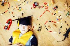 Mała śliczna preschooler chłopiec wśród zabawki lego w magisterski kapeluszowy uśmiecha się pozować emocjonalny w domu, stylu życ Zdjęcie Stock