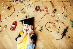 Mała śliczna preschooler chłopiec wśród zabawki lego w magisterski kapeluszowy uśmiecha się pozować emocjonalny w domu, stylu życ Obrazy Royalty Free