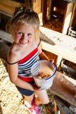 Mała śliczna wiejska dziewczyna trzyma plastikowego wiadro z jajkami obrazy stock