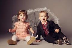 Mała śmieszna chłopiec i dziewczyna pod parasolem obraz royalty free