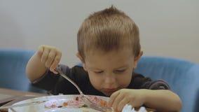 Mała śmieszna chłopiec je naczynie nieudolnego z dużymi oczami 4K zbiory wideo