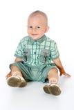 Mała śmieszna chłopiec patrzeje kamerę, obsiadanie i ono uśmiecha się, Fotografia Royalty Free