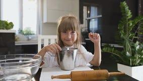 Mała śmieszna dziewczyna jest gotująca mąkę w pucharze i mieszająca brunetek błękitny boże narodzenia przyglądają się żeńskiego p zbiory