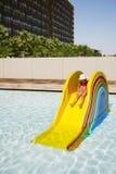 Mała śmieszna dziewczyna na kolorowym mini waterslide w jaskrawym basenie Zdjęcia Stock