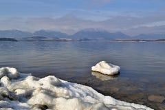 Mała śnieżna wyspa w jeziornym pobliskim brzeg z górami w plecy Obrazy Royalty Free