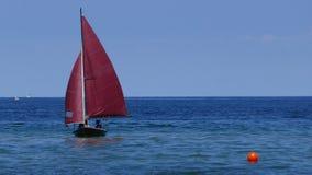 Mała żaglówka, stary żeglowania dinghy z zmrokiem - czerwień żagle unoszą się w błękitnym morzu Obraz Royalty Free
