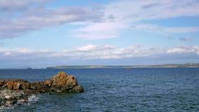 Mała żeglowanie łódź unosi się w morzu Skalisty brzeg jest widoczny w odległości zbiory