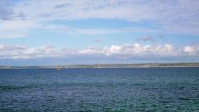 Mała żeglowanie łódź unosi się w morzu Skalisty brzeg jest widoczny w odległości zbiory wideo