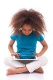Mała afrykańska azjatykcia dziewczyna używa pastylka komputer osobisty Zdjęcia Royalty Free