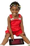 Mała amerykanin afrykańskiego pochodzenia dziewczyna używa pastylka komputer osobistego Obrazy Stock