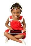 Mała amerykanin afrykańskiego pochodzenia dziewczyna używa pastylka komputer osobistego Zdjęcia Royalty Free