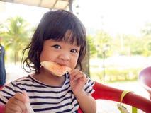 Mała Asia dziewczyna budzi się up na ranku Ona łasowanie grzanka z truskawkowym dżemem mała Asia dziewczyna szczęśliwy i dobry zd Obrazy Royalty Free