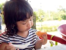 Mała Asia dziewczyna budzi się up na ranku Ona łasowanie grzanka z truskawkowym dżemem mała Asia dziewczyna szczęśliwy i dobry zd Obraz Stock