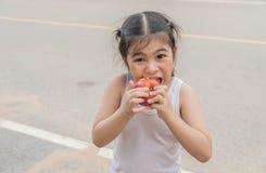 Mała Azjatycka dziewczyna cieszy się je jabłka Na drodze Zdjęcie Royalty Free
