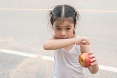 Mała Azjatycka dziewczyna cieszy się je jabłka Na drodze Fotografia Stock