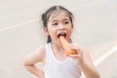 Mała Azjatycka dziewczyna cieszy się je marchewki Na drodze Obraz Stock