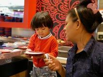Mała Azjatycka dziewczynka cieszy się podnoszący surowych składniki dato che jej matki dla hotpot kucharstwa, porcja na poruszają zdjęcie royalty free